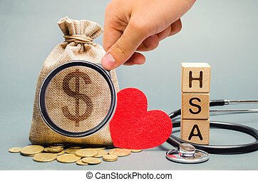 Wooden blocks with the word HSA and money bag with stethoscope. Health savings account. Health care. Health insurance. Investments. Tax-free medical expenses. Coins and dollar sign. Red heart