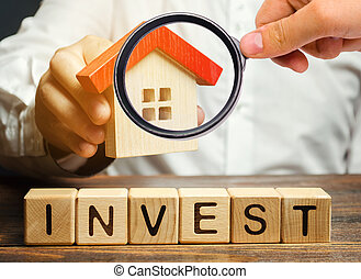 Wooden blocks with the word Invest and house in the hands of a businessman. The concept of investing in real estate construction. Effective investment. Buying apartments. Business and finance