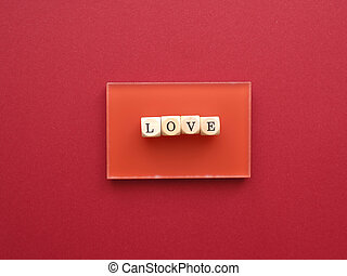 Wooden blocks with the word love on a red background