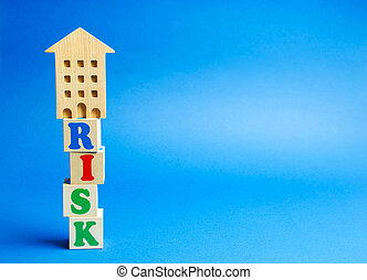 Wooden blocks with the word Risk and a miniature house. Real estate investment risk. Risky investments. Loss of property for non-payment. Debts. Mortgage tax. Fraudulent schemes.