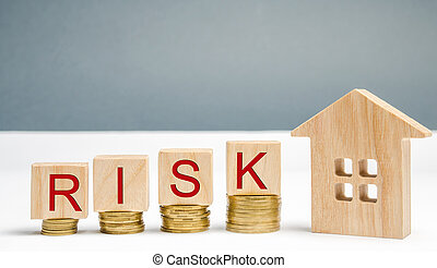 Wooden blocks with the word Risk and coins with a house. The concept of risk, loss of real estate. Property insurance. Loans secured by home, apartment. Financial risks, litigation. Debt growth