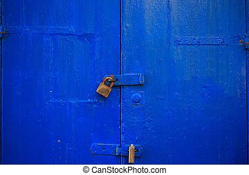 Wooden blue door background locked with two rusty padlocks. Aged, closed entrance, close up view with details.