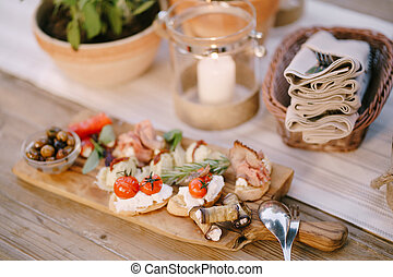 Wooden board for cutting with cold cuts, bread and olives on a blurred background of the festive table.