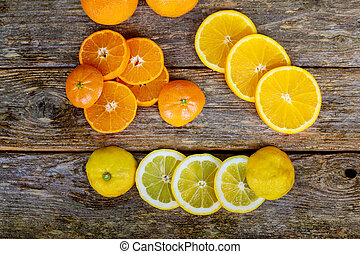 Wooden board with different citrus fruits on table, top view