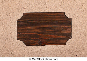 Wooden board with place for text on the sand. Top view.