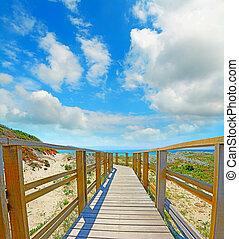 wooden boardwalk under a cloudy sky in Capo Testa, Sardinia