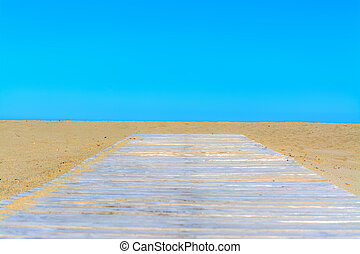Wooden boardwalk on the beach under a blue sky in Sardinia