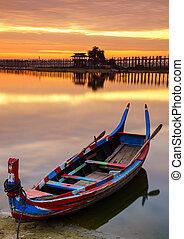 Wooden boat in Ubein Bridge at sunrise, Mandalay, Myanmar...