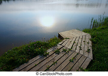 Wooden boat landing pier by lake at sunset