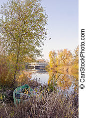 Wooden boat locked near river. Autumn morning view
