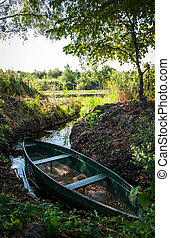 Wooden boat moored in the bay of the river among the reeds