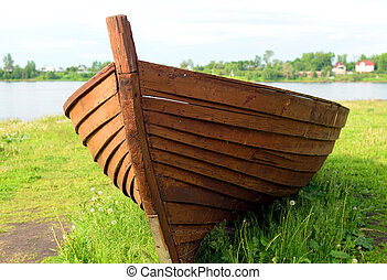 Wooden boat on coast of river.