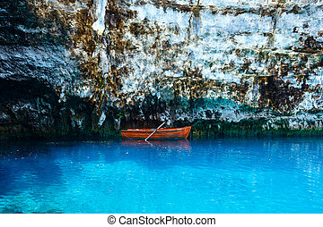 Wooden boat on lake surface.
