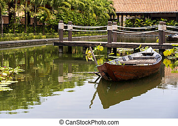 Wooden boat on the pond near the pier in a tropical garden in Danang, Vietnam