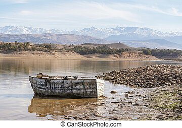 Wooden boat on the shore of lake with mountains in the background, Morocco