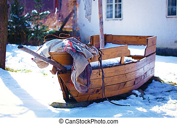 Wooden boat on the snow in winter.