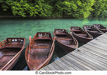 Wooden boats at the pier on the lake in the evening light.