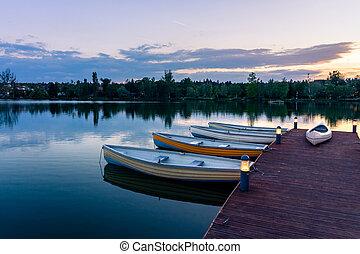 wooden boats on a calm lake called Csonakazo Lake in Szombathely Hungary at dusk after sunset