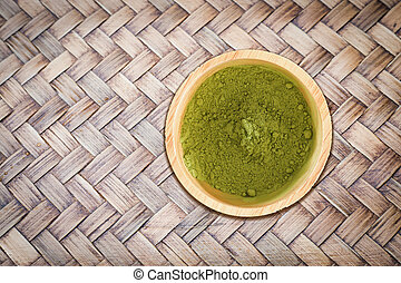 Wooden bowl of green tea powder on bamboo craft texture