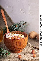 Wooden bowl of yogurt with rolled oats and nuts and standing spoon on burlap on white wall background.