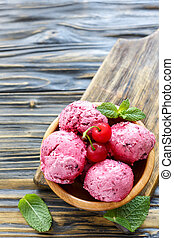 Wooden bowl with balls of cherry ice cream.