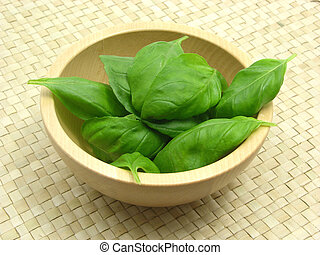 Wooden bowl with basil on rattan underlay