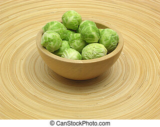 Wooden bowl with brussels sprouts on bamboo plate