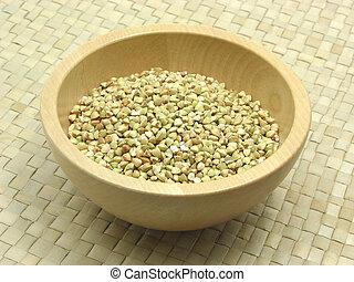 Wooden bowl with buckwheat on rattan underlay