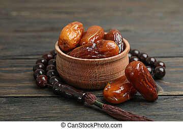 Wooden bowl with dates and prayer beads on wooden background