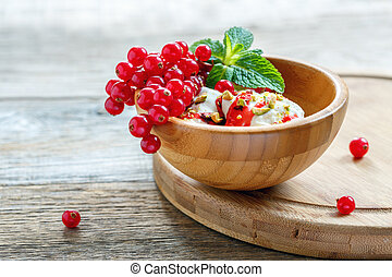 Wooden bowl with ice cream, red currant and mint.