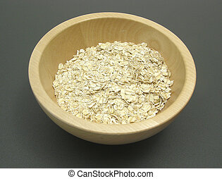 Wooden bowl with oat flakes on a dull matting