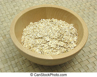 Wooden bowl with oat flakes on rattan underlay