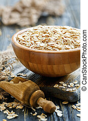 Wooden bowl with oat flakes.