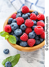 Wooden bowl with raspberries and blueberries.