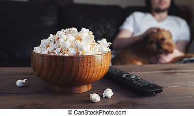 Wooden bowl with salted popcorn and TV remote on wooden table. In the background, a man with a red dog watching TV on the couch