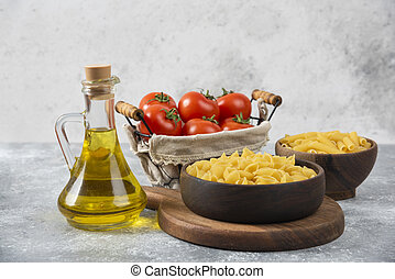 Wooden bowls of raw various pasta and fresh tomatoes on marble background