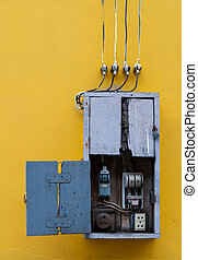 Wooden box, electric control equipment in the factory on yellow vintage concrete wall background. Manual cut out with old design. Safety in home and factory industrial concept.
