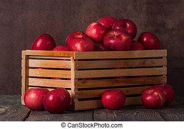 Wooden box full of apples in drops of water on dark