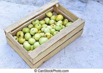 Wooden box full of green ripe apples in autumn
