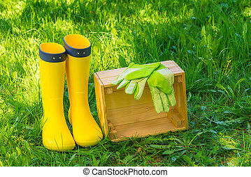 wooden box, green gloves and yellow rubber boots on lush grass in the backyard of the house