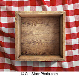 Wooden box on red picnic tablecloth top view