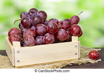 Wooden box with red grapes