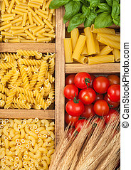 Wooden box with various classic italian pasta and basil with cherry tomatoes.