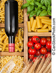 Wooden box with various classic italian pasta and basil with tomatoes and bottle of red wine.