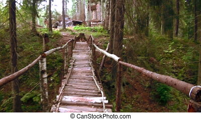 Wooden bridge across the stream in the forest