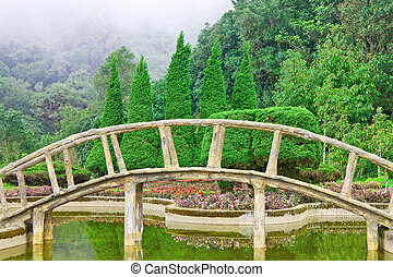 Wooden bridge and garden among valley