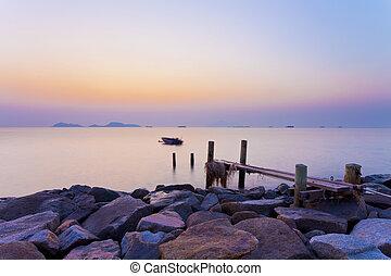 Wooden bridge at sunset along coast