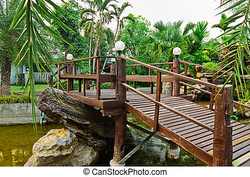 Wooden bridge cross the concrete stream in garden
