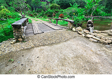 Wooden bridge cross the stream and garden