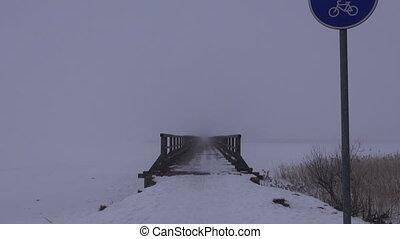 wooden bridge in dark winter mist